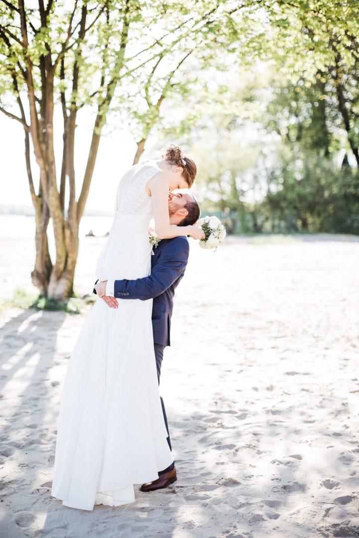 Braut und Bräutigam am Elbstrand unter Bäumen im Gegenlicht