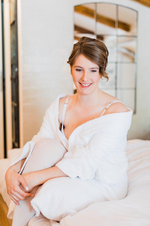 Braut sitzt auf Bett beim Getting Ready