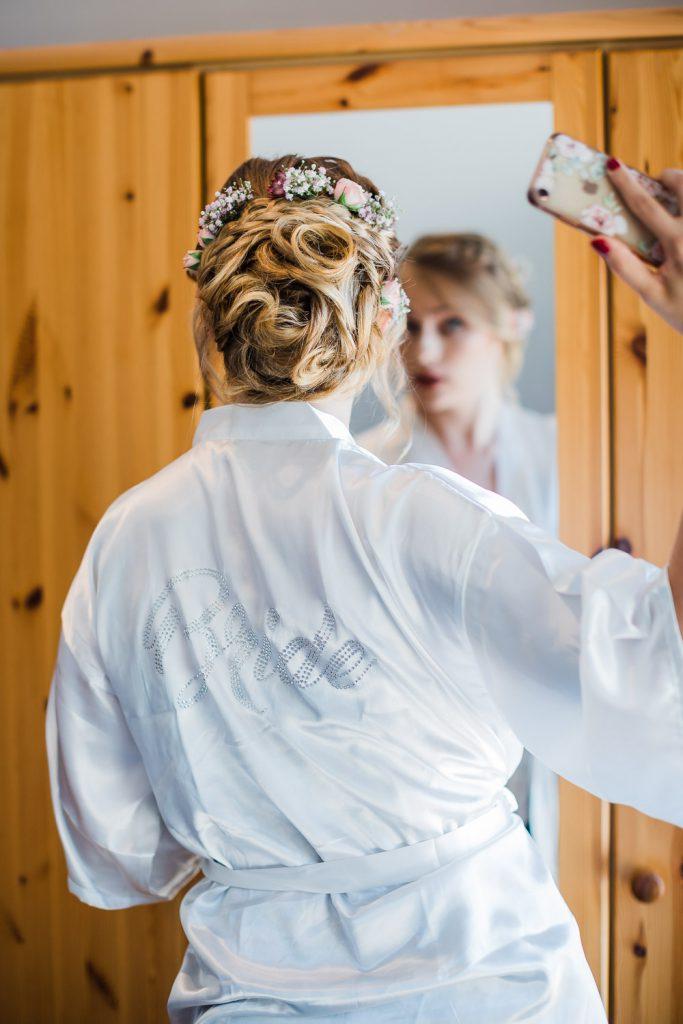 Braut betrachtet sich mit iPhone im Spiegel