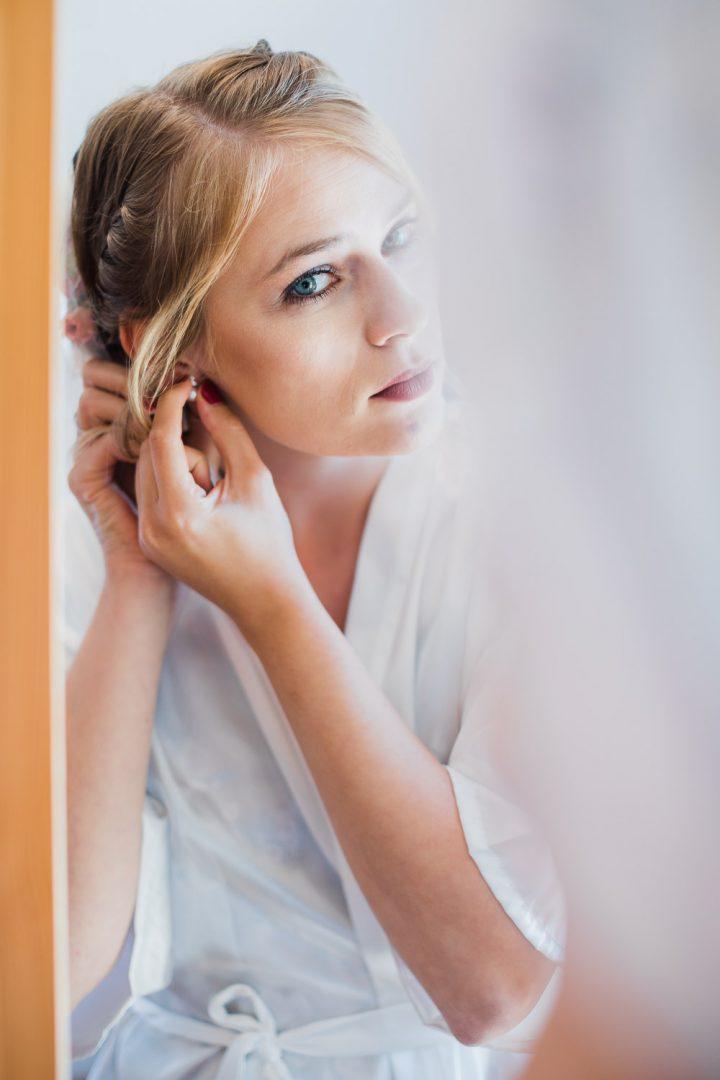 Braut steht vor dem Spiegel und steckt sich Ohrringe an