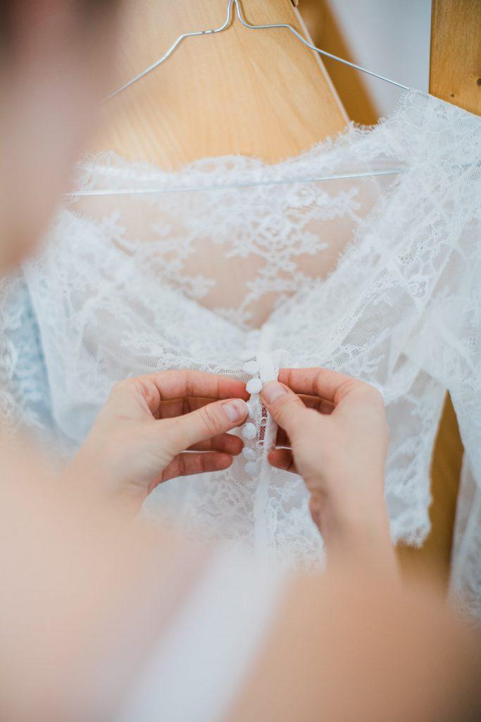 Braut öffnet Knöpfe ihres Brautkleides