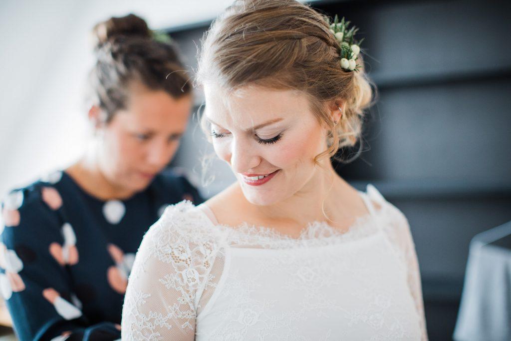 Trauzeugin schließt Braut das Brautkleid